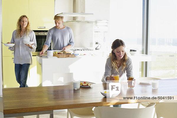 Mädchen beim Frühstück auf dem Esstisch mit ihren Eltern im Hintergrund