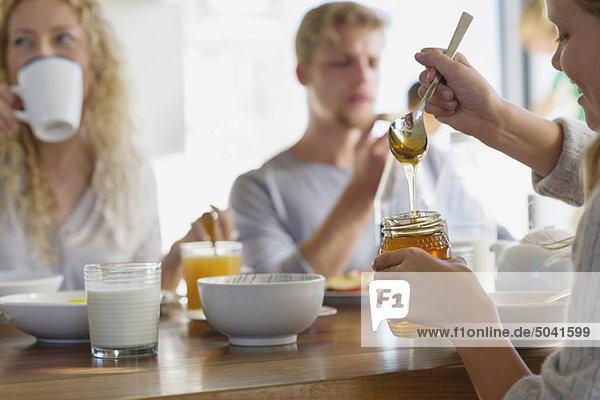 Familienfrühstück zu Hause mit Fokus auf ein Mädchen  das Honig mitnimmt.