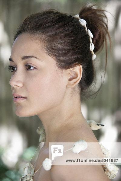 Seitenprofil einer schönen jungen Frau mit Muschelkette