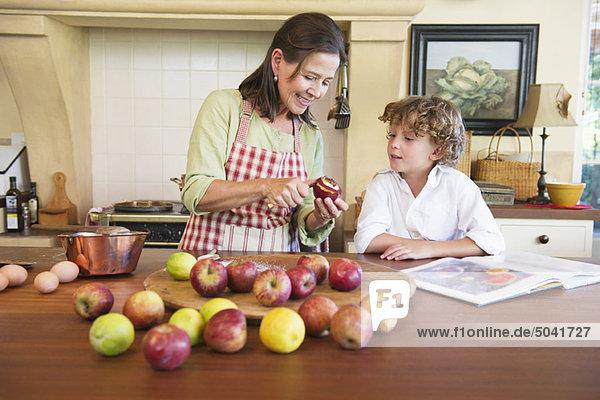 Großmutter und kleiner Junge beim Obstschälen zu Hause