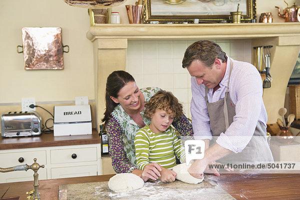 Süßer kleiner Junge und seine Eltern kneten Teig in der Küche.