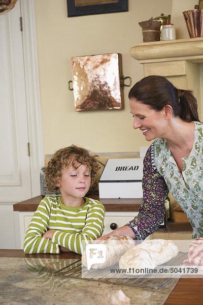 Süßer kleiner Junge und Mutter beim Brotbacken in der Küche