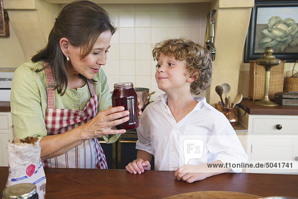 Großmutter und kleiner Junge riechenden Honig in der Küche