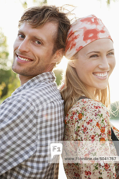 Porträt eines Paares,  Rücken an Rücken stehend und lächelnd