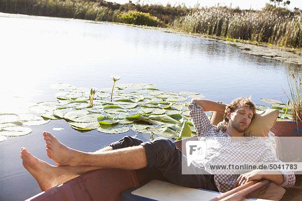 Junger Mann schläft im Boot