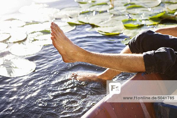 Mann liegt in einem Boot und taucht seine Beine in einen Teich.