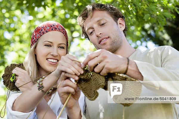 Junges Paar strickt zusammen und lächelt