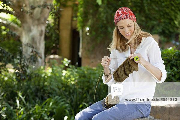 Fröhliche junge Frau beim Stricken