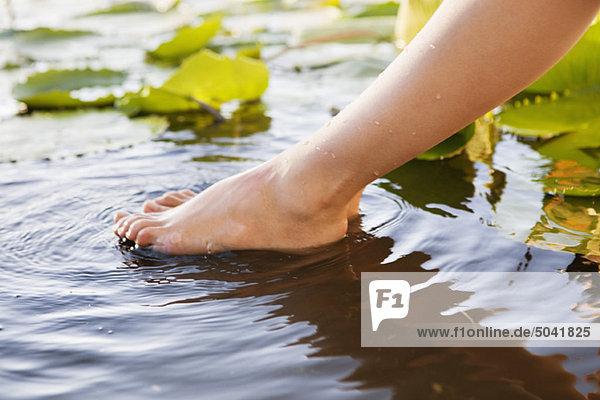 Nahaufnahme eines Frauenbeins im Teich
