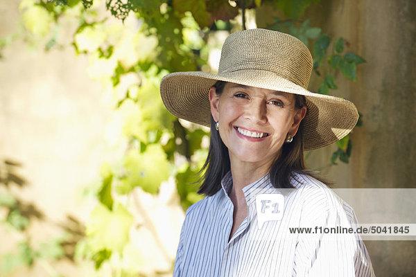 Porträt einer älteren Frau mit Hut und Lächeln