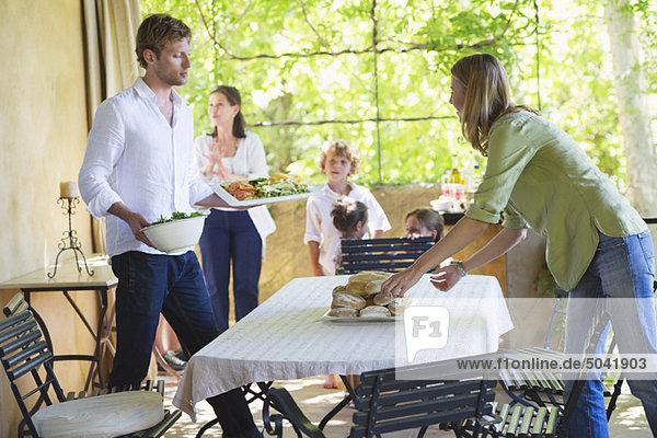 Essen auf dem Esstisch arrangieren mit der Familie im Hintergrund