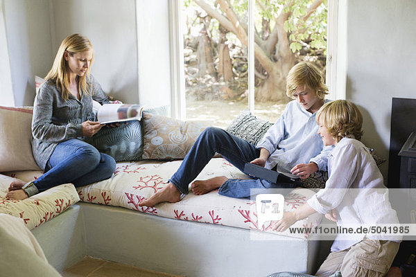 Kinder  die ein digitales Tablett benutzen  während die Mutter das Magazin im Haus liest.