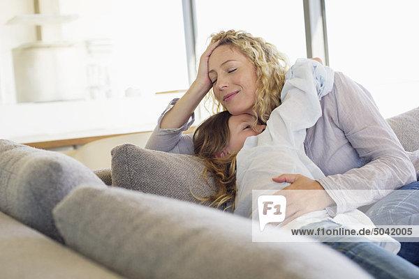 Mittlere erwachsene Frau und ihre Tochter umarmen sich auf einer Couch.