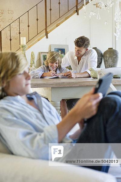Mann  der den kleinen Jungen mit dem Bruder unterrichtet  der das digitale Tablett im Vordergrund im Haus benutzt.