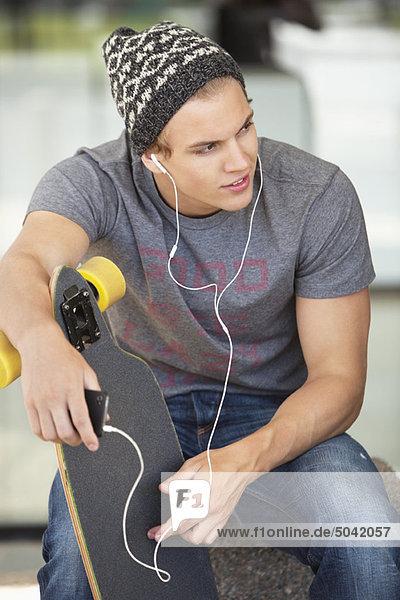 Mann hält ein Skateboard und hört Musik auf dem Handy.