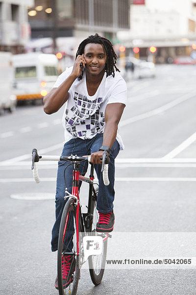 Lächelnder Mann beim Radfahren am Handy