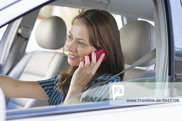Schöne junge Frau  die beim Autofahren über das Handy spricht.