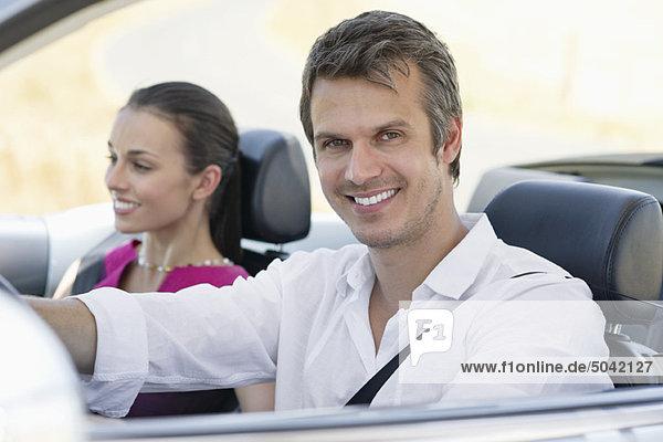 Porträt eines Paares  das ein Cabriolet fährt