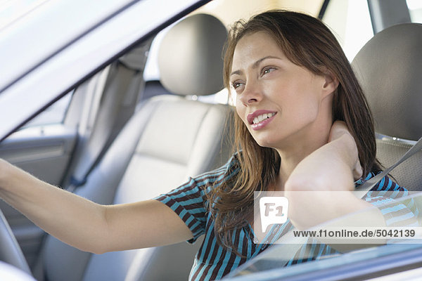 Müde junge Frau  die beim Autofahren den Nacken reibt