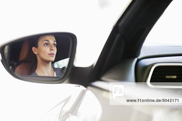 Spiegelung einer jungen Frau auf der Seitenscheibe eines Autos während einer Probefahrt
