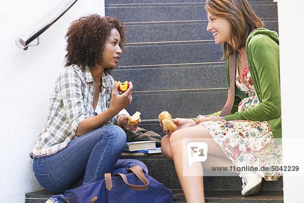 Seitenprofil der Universitätsstudenten beim Essen auf der Treppe in der Universität