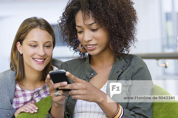Lächelnde Frauen mit dem Handy in der Universität