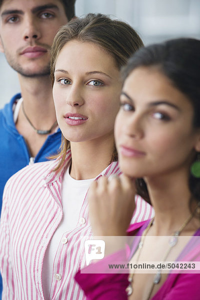 Portrait of three university students standing in a line with focus on a woman