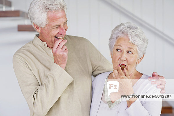 Senior couple eating chocolate at home