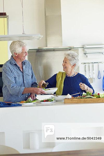 Seniorenpaar bei der Zubereitung von Speisen in der heimischen Küche