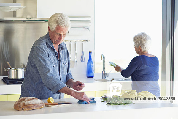 Seniorenpaar beim Putzen der Küche