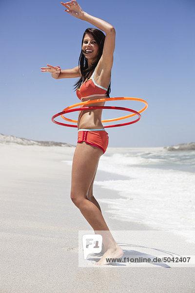 Frau spielt mit Plastikreifen am Strand