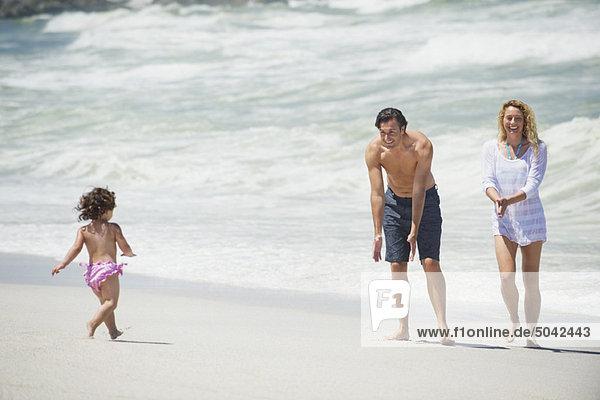Glückliche Familie beim Spielen am Strand