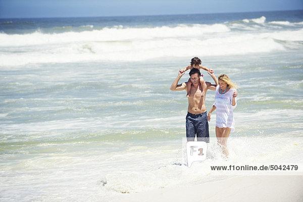 Mann  der seine Tochter auf den Schultern trägt  mit Frau  die mit ihm geht.