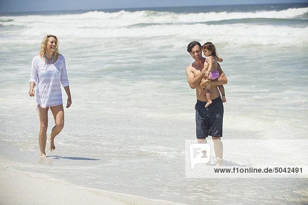 Ein Paar  das mit seiner Tochter am Strand spazieren geht.