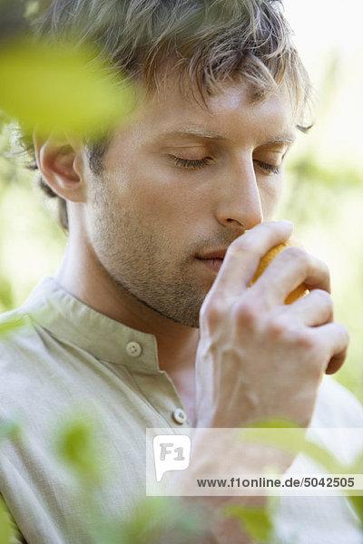 Nahaufnahme eines Mannes  der an einer Zitrone riecht. Nahaufnahme eines Mannes, der an einer Zitrone riecht.