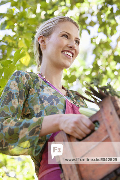 Lächelnde Frau hält eine Kiste mit Gemüse. Lächelnde Frau hält eine Kiste mit Gemüse.