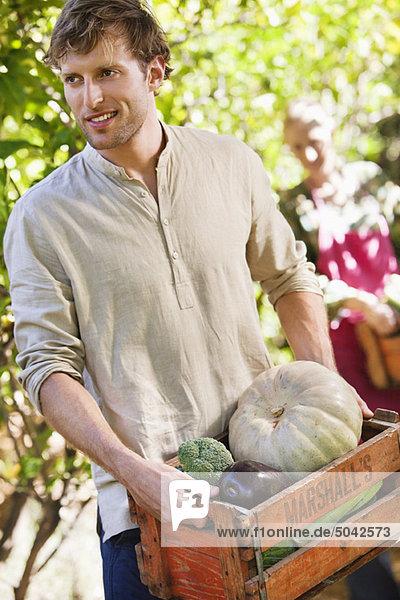 Lächelnder Mann hält eine Kiste mit Gemüse. Lächelnder Mann hält eine Kiste mit Gemüse.
