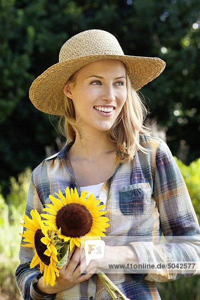 Glückliche junge Frau mit Sonnenblumen auf dem Feld