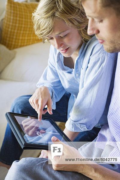 Ein Mann und ein kleiner Junge beim Betrachten des digitalen Tabletts