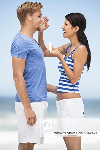 Frau  die Sonnencreme auf das Gesicht des Mannes aufträgt.