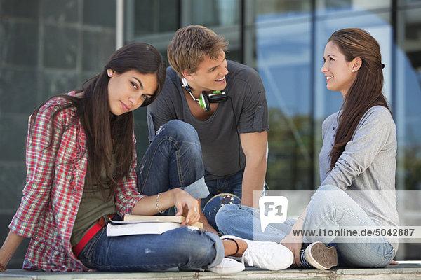 Junge Schüler diskutieren und lächeln