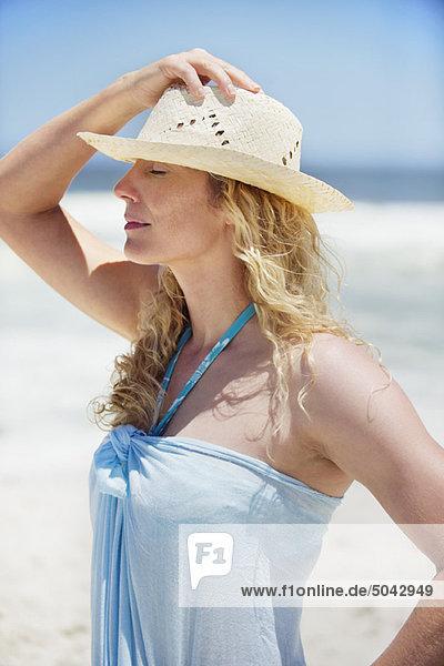 Mittlere erwachsene Frau mit Sonnenhut am Strand