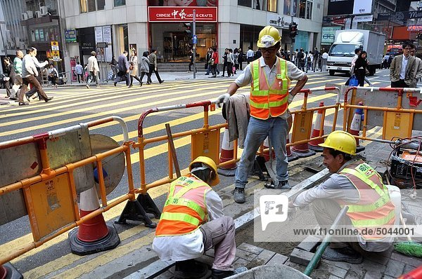 Hong Kong: men at work fixing pipes along a street in Central