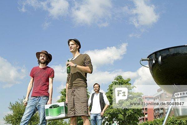 Drei Männer bei einer Grillparty