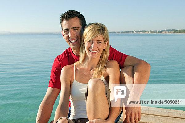 Glückliches Paar auf einer Mole am Meer
