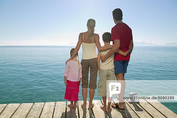Rückansicht der auf dem Steg stehenden Familie