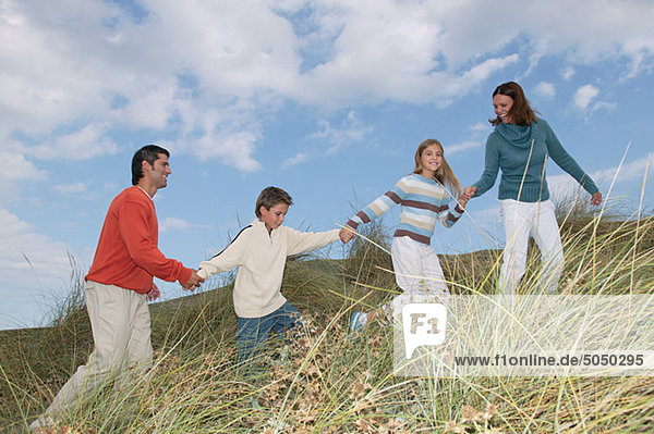 Familie geht Hand in Hand über die Düne