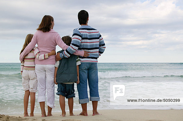 Rückansicht der am Meer stehenden Familie