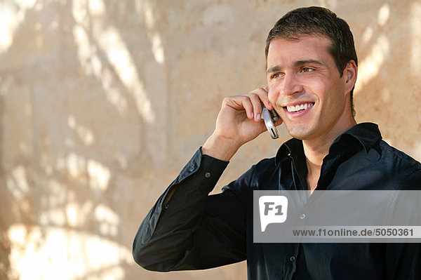 Man in a black shirt using cellphone