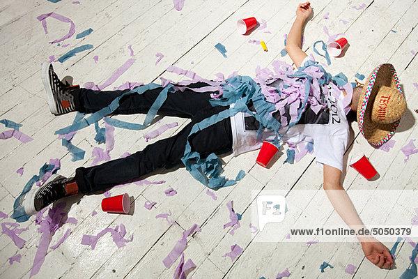 Mann  der auf dem Boden liegt und auf der Party mit Luftschlangen bedeckt ist.